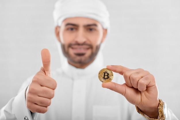 Przystojny arabski mężczyzna z bitcoinem