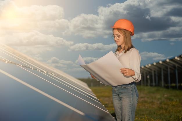 Przystojny architekt kobieta bada mapę roboczą lub plan projektu planu