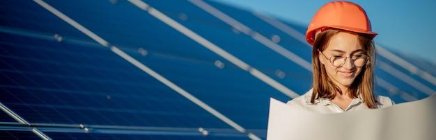 Przystojny architekt kobieta bada szkic mapy lub plan projektu plan, aktywność pracownika patrząc w farmie ogniw fotowoltaicznych lub pola paneli słonecznych.