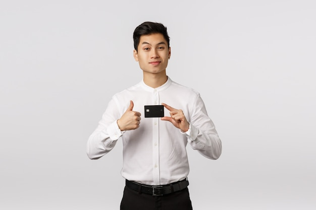 Przystojny asertywny azjatycki młody biznesmen poleca bank, trzymając kartę kredytową wykonaj kciuk, uśmiechnij się i podnieś brew z dumnym, zadowolonym wyrazem twarzy