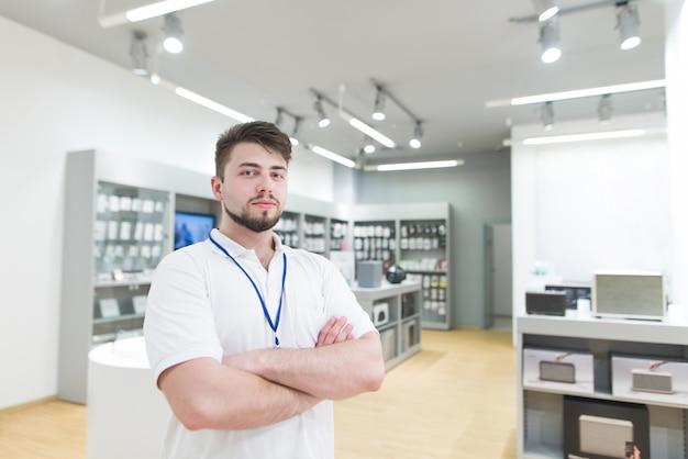 Przystojny asystent człowieka stoi na powierzchni sklepu technologicznego