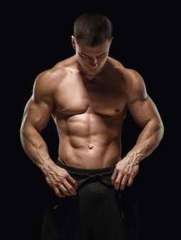 Przystojny atletyczny facet przygotowuje się do ćwiczeń. obraz na białym tle, czarne tło.