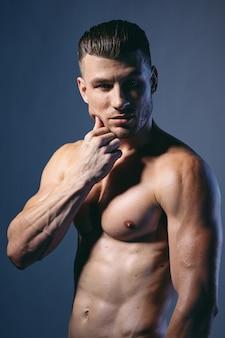 Przystojny atletyczny mężczyzna ciało z mięśniami pozuje wewnątrz