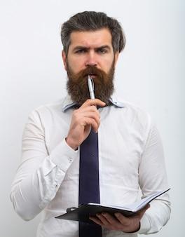 Przystojny atrakcyjny biznesowy mężczyzna podniósł pióro i notatnik w ręce, na białym tle.