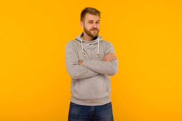 Przystojny atrakcyjny europejski mężczyzna w szarej bluzie z kapturem na żółtym tle - obraz