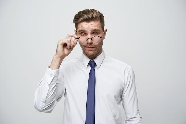 Przystojny, atrakcyjny młody człowiek z stylową fryzurą koryguje okulary