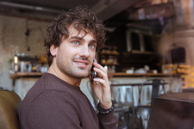 Przystojny, atrakcyjny, uśmiechnięty, kręcony, szczęśliwy, radosny zadowolony facet w brązowej bluzce siedzący w kawiarni i rozmawiający na telefonie komórkowym
