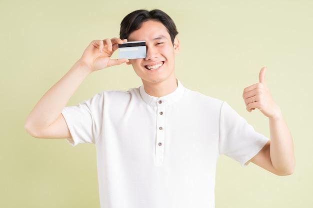 Przystojny azjata uśmiecha się i zasłania oczy kartą kredytową, trzymając kciuki do góry