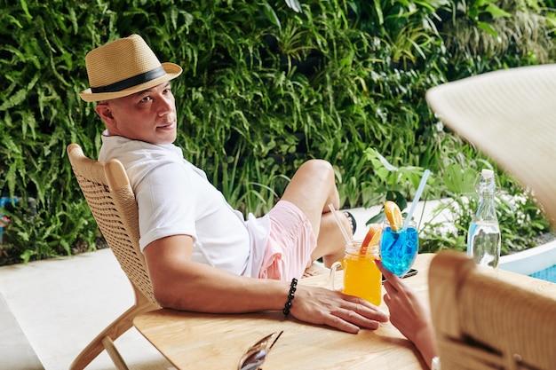 Przystojny azjata w kapeluszu pije koktajle i rozmawia ze swoją dziewczyną, gdy odpoczywają przy basenie w słoneczny dzień