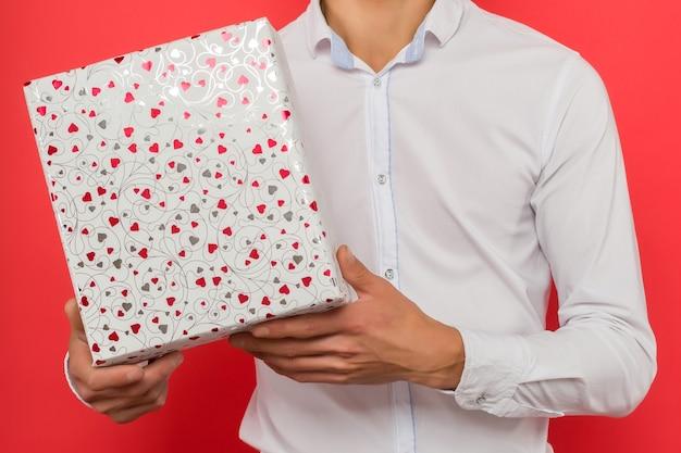 Przystojny azjatycki biznesmen trzyma pudełko na czerwonym tle