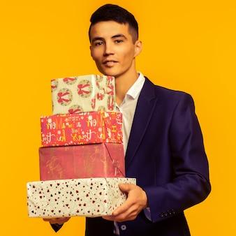 Przystojny azjatycki biznesmen trzymający pudełko na żółtym tle