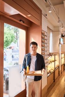 Przystojny azjatycki mężczyzna kupuje piekarnię na przerwę na kawę po południu. piekarnia i przerwa na kawę.