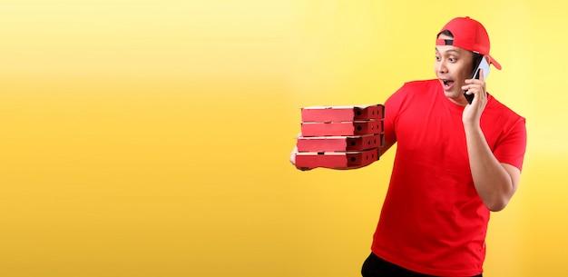 Przystojny azjatycki mężczyzna w czerwonej czapce, dając zamówienie żywności włoskiej pizzy w kartonach na białym tle trzymając telefon komórkowy z pustym białym pustym ekranie.