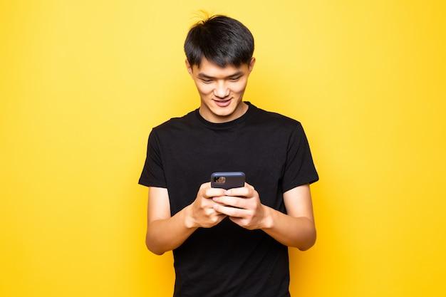 Przystojny azjatycki młody człowiek używa smartphone