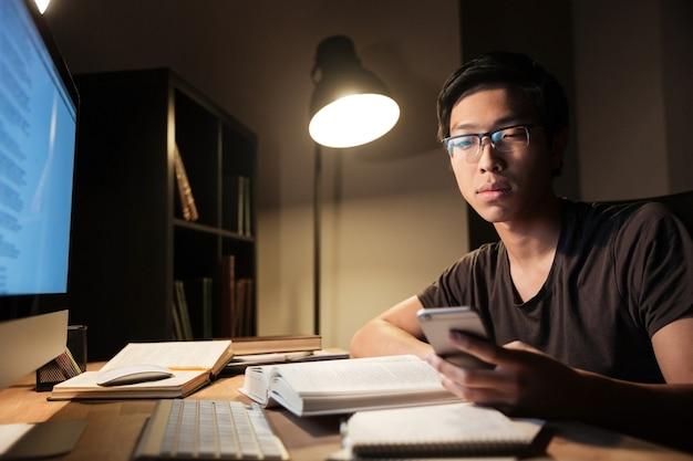 Przystojny azjatycki młody mężczyzna w okularach, studiujący i używający smartfona wieczorem w domu