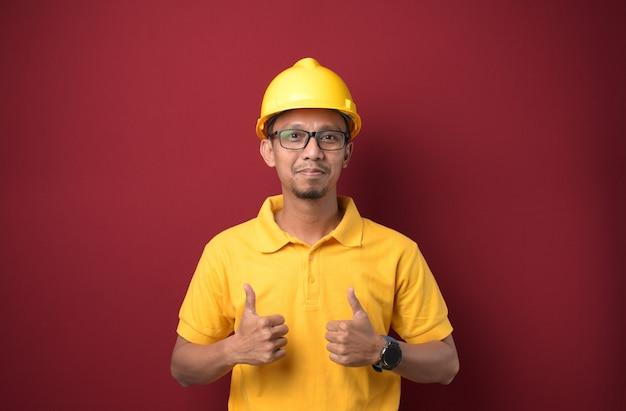Przystojny azjatycki pracownik mężczyzna nosi hełm, uśmiechając się i kciuk w górę na na białym tle czerwonym tle.
