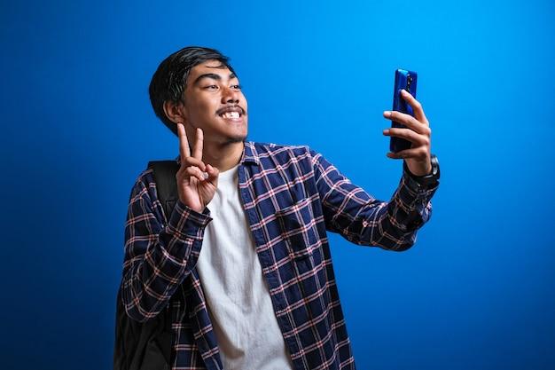 Przystojny azjatycki student z flanelową koszulą, biorący selfie na smartfonie, wideorozmowy z przyjaciółmi za pośrednictwem aplikacji, komunikator na telefon komórkowy, uśmiechnięty zadowolony, niebieskie tło