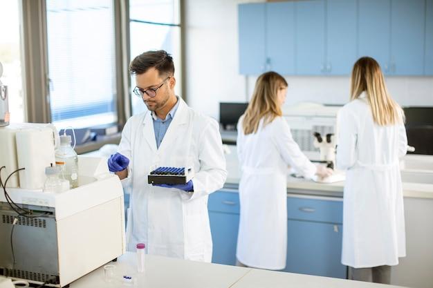 Przystojny badacz w ochronnej odzieży roboczej stoi w laboratorium i analizuje próbki cieczy