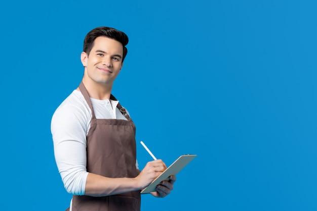 Przystojny barista na sobie rozkaz pisania fartuch w schowku
