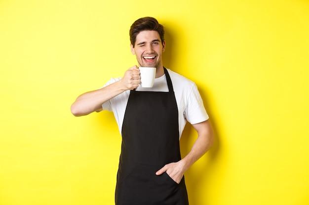 Przystojny barista pije filiżankę kawy i mruga, zaprasza do kawiarni, stoi nad żółtą ścianą