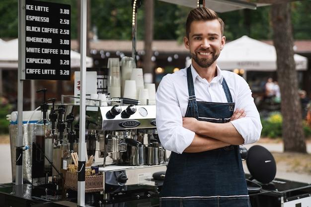 Przystojny barista podczas pracy w swojej ruchomej ulicznej kawiarni