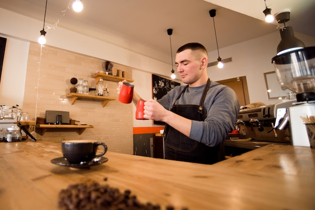 Przystojny barista przygotowywa filiżankę kawy dla klienta w sklep z kawą.
