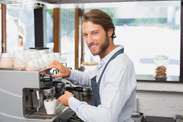 Przystojny barista robi filiżance kawy