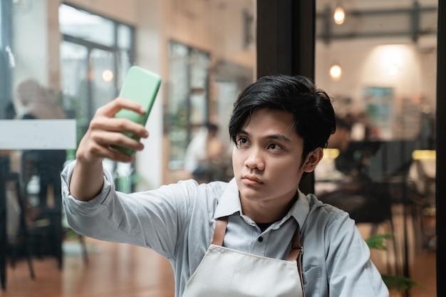 Przystojny barista selfie podczas przerw w pracy używa aparatu w smartfonie