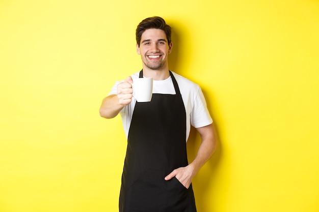 Przystojny barista w czarnym fartuchu daje filiżankę kawy i uśmiechnięty, stojąc nad żółtą ścianą
