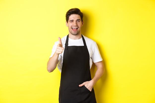Przystojny barista w czarnym fartuchu wita gości w kawiarni, wskazując pistoletem na palec i mrugając, stojąc przed żółtą ścianą