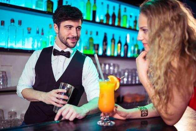 Przystojny barman flirtuje z młodą kobietą