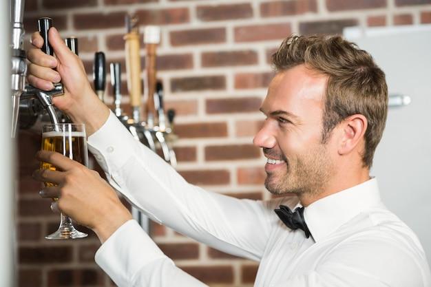 Przystojny barman nalewa kufel piwa