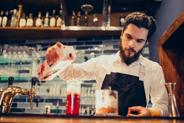 Przystojny barman pić i koktajle w kasie