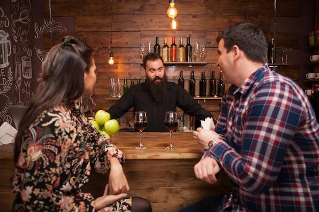 Przystojny barman rozmawia z klientami przy barze w pubie. hipsterski pub.