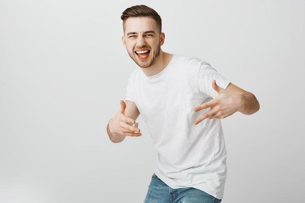 Przystojny beztroski facet tańczy hip hop i dobrze się bawi