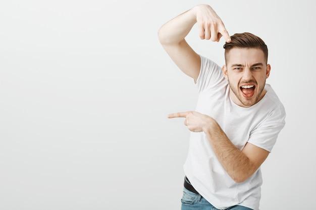 Przystojny beztroski facet tańczy hip hop i wskazuje w lewo