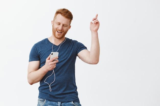 Przystojny beztroski i radosny nowoczesny brodaty mężczyzna w niebieskiej koszulce podnoszący rękę w tanecznym ruchu, trzymający smartfon, słuchający piosenek w słuchawkach