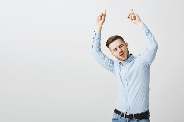 Przystojny beztroski pracownik biurowy tańczy do muzyki w słuchawkach bezprzewodowych i wskazuje palcami w górę