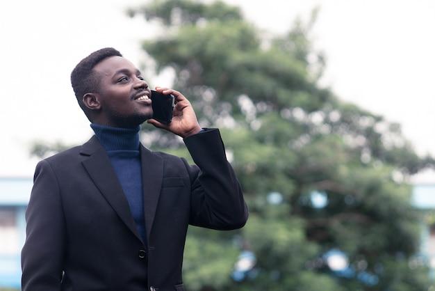 Przystojny biznesmen afryki za pomocą smartfona w modnym formalnym czarnym garniturze. facet z brodą ubrany w niebieski długi rękaw lub sweter