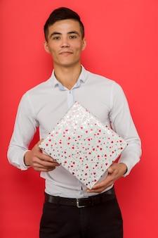Przystojny biznesmen azjatyckich gospodarstwa pudełko na czerwonym tle