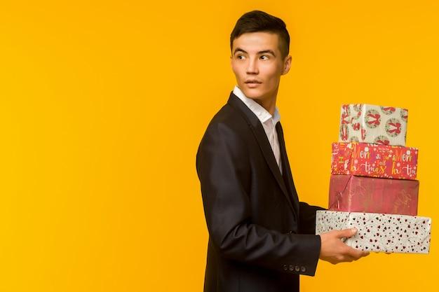 Przystojny biznesmen azjatyckich gospodarstwa pudełko na żółtym tle - obraz
