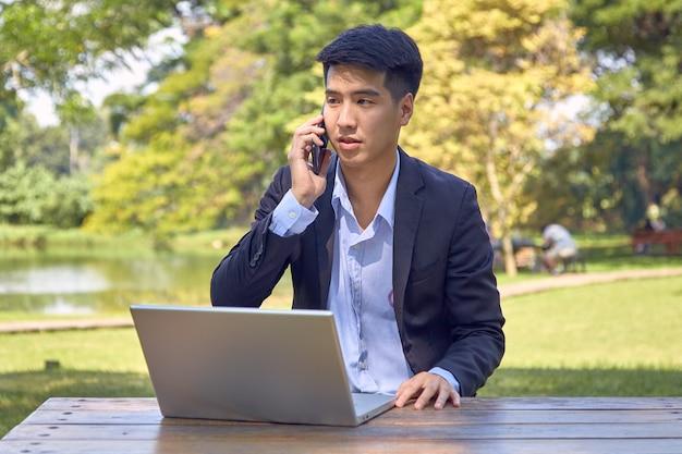 Przystojny biznesmen azjatyckich za pomocą laptopa