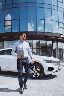 Przystojny biznesmen białym samochodem