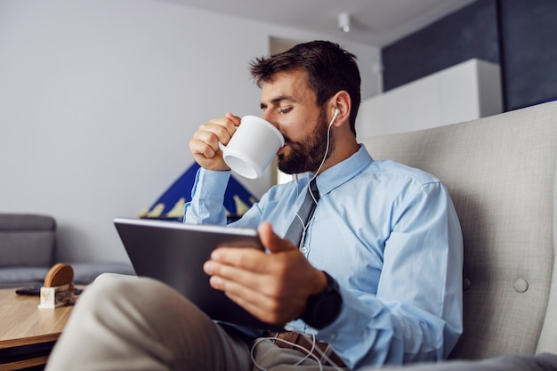 Przystojny biznesmen brodaty picia kawy i korzystania z tabletu, siedząc w domu na krześle.