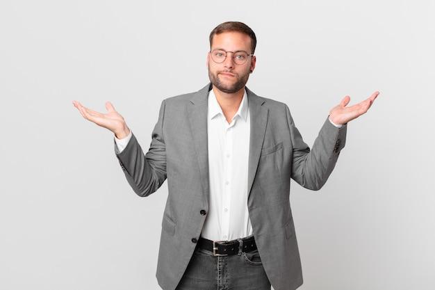 Przystojny biznesmen czuje się zakłopotany, zdezorientowany i wątpi