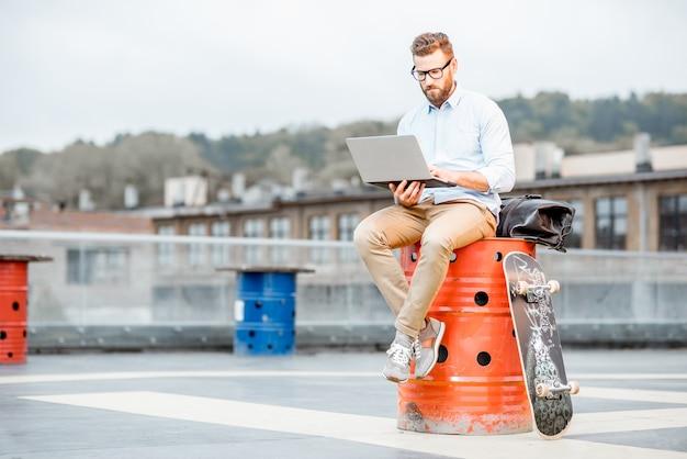 Przystojny biznesmen hipster pracy z laptopem na placu zabaw na dachu budynku przemysłowego. koncepcja biznesowa stylu życia