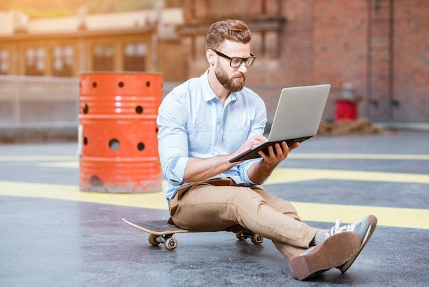 Przystojny biznesmen hipster pracy z laptopem siedząc na deskorolce na tle dachu. koncepcja biznesowa stylu życia