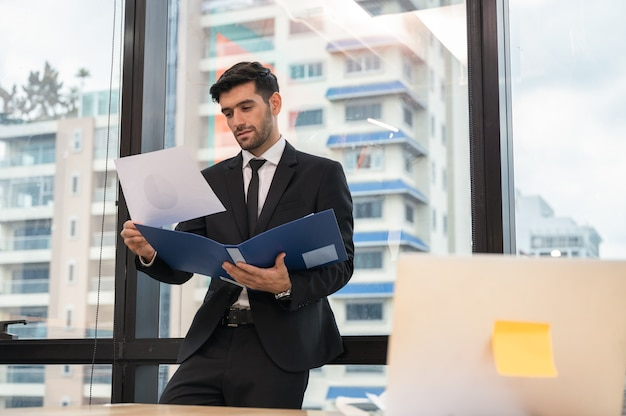 Przystojny biznesmen kaukaski stojąc i analizując sprawozdanie finansowe w nowoczesnym biurze w dzielnicy biznesowej