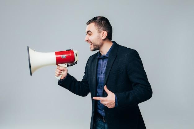 Przystojny biznesmen krzycząc przez megafon na białym tle