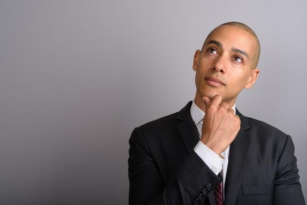 Przystojny biznesmen łysy ubrany w garnitur na szaro